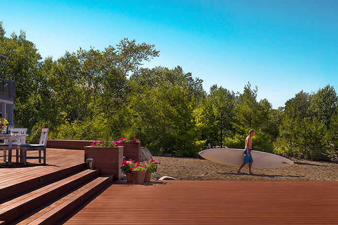 lifestyle shot of Greenworld Mahogany deck at cottage, senior male with surf board, commercial, exterior on location